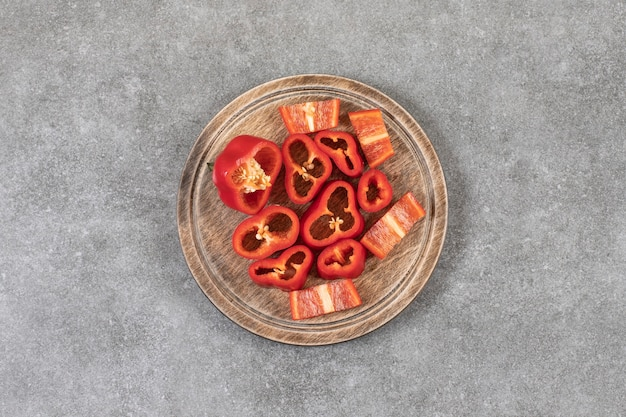 Assiette en bois de poivrons rouges frais tranchés sur une surface en marbre.