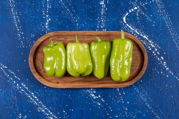 Assiette en bois de poivrons verts sur une surface en marbre