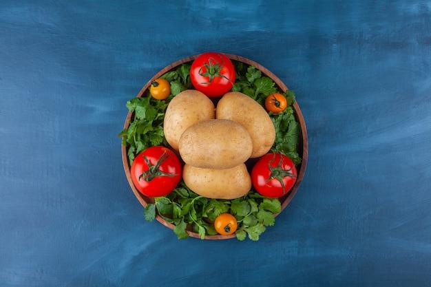 Assiette en bois de pommes de terre fraîches et tomates sur une surface bleue.