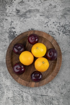 Une assiette en bois de prunes violettes et de citrons frais sur une table en pierre.