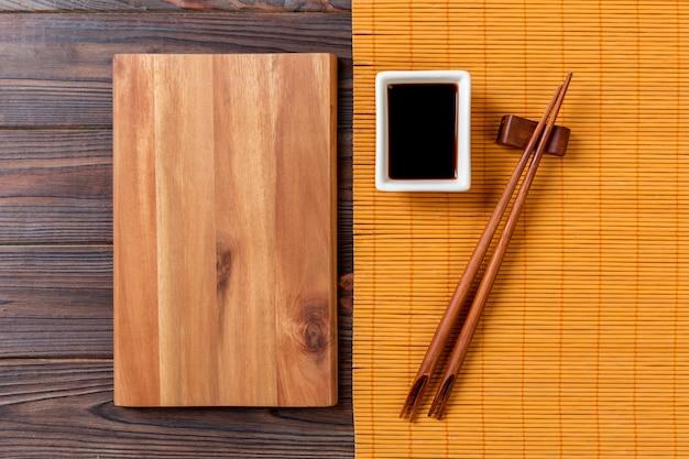 Assiette en bois rectangulaire vide avec des baguettes pour sushi et sauce soja sur bois