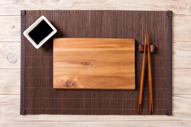 Assiette en bois rectangulaire vide pour sushi avec sauce et baguettes sur la table en bois, vue de dessus