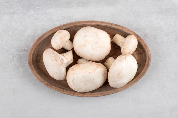 Une assiette en bois remplie de champignons frais placés sur une surface en pierre