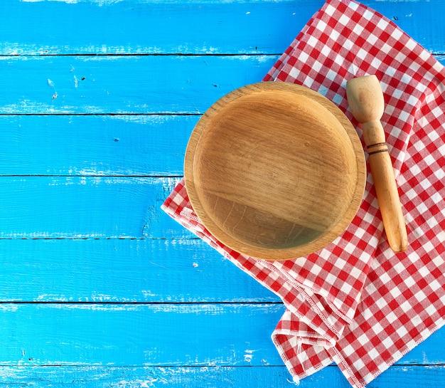 Assiette en bois ronde vide et cuillère sur une serviette en tissu blanc rouge