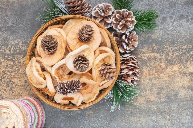 Assiette en bois de rondelles de pommes séchées et de pommes de pin sur pierre.
