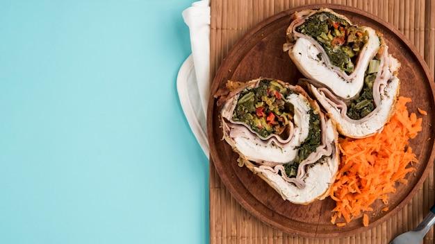 Assiette en bois avec rouleau de poulet et carotte