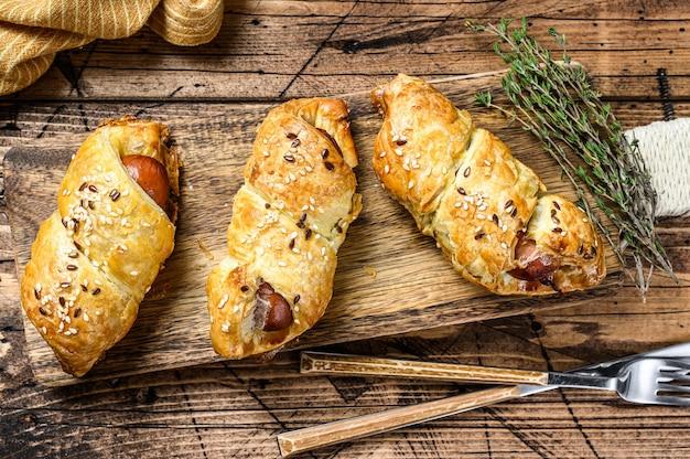 Assiette en bois avec des rouleaux de saucisse dans la pâte
