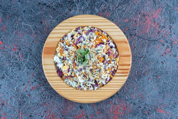Une assiette en bois avec salade de légumes sur une surface en marbre