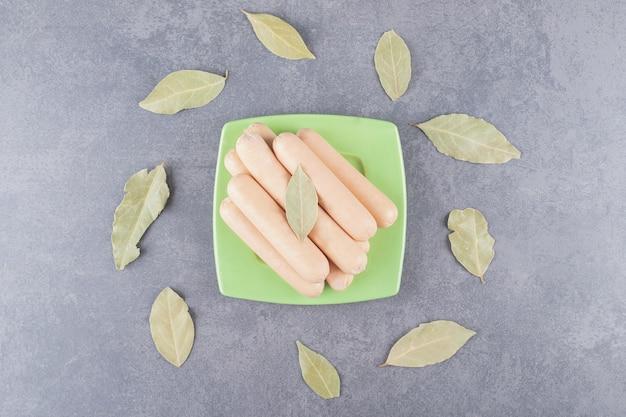 Une assiette en bois avec des saucisses bouillies et des feuilles de laurier