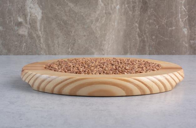 Assiette en bois avec un tas de riz à grain long sur marbre.