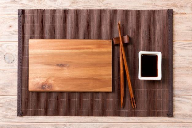 Assiette en bois vide avec des baguettes pour sushi et sauce soja sur bois.