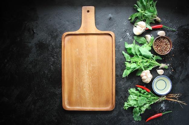 Assiette en bois vide sur culinaire en métal noir