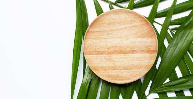 Assiette en bois vide sur les feuilles de palmier tropical sur fond blanc. vue de dessus
