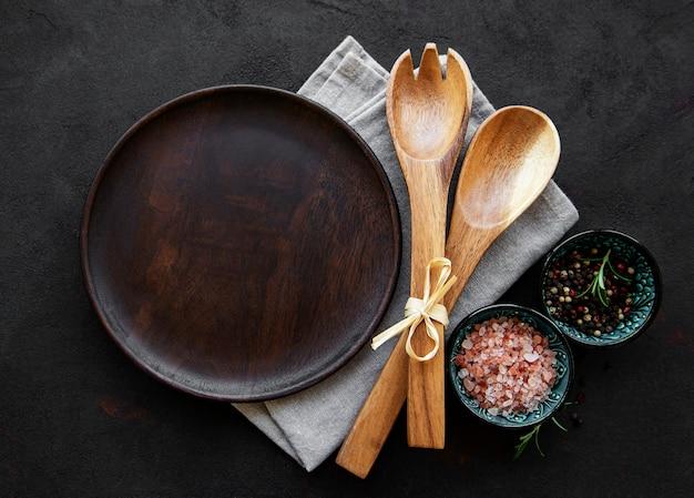 Assiette en bois vide sur fond noir