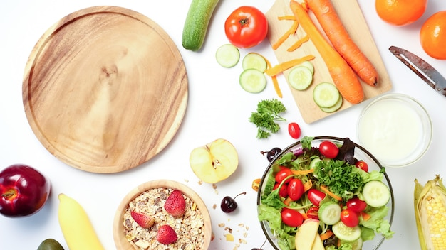 Assiette en bois vide, salade de légumes, muesli et fruits frais sur fond blanc