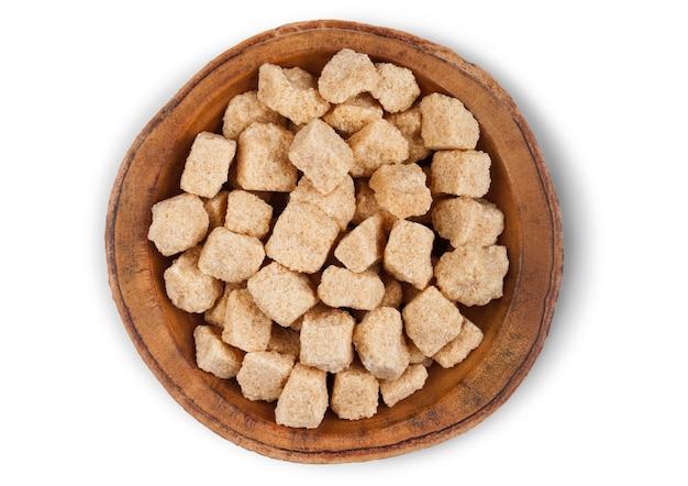 Assiette de bol en bois de cubes de sucre non raffiné brun naturel sur blanc.
