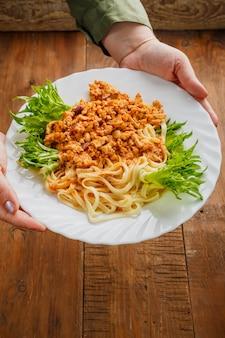 Une assiette de bolognaise décorée d'herbes dans les mains des femmes. photo verticale