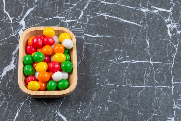 Assiette de bonbons colorés sur fond de marbre.