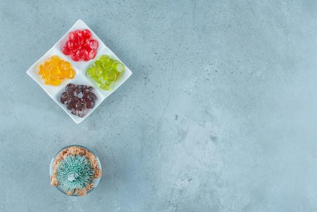Assiette de bonbons durs assortis à côté d'un petit porte-bonbons avec des bonbons au pop-corn et une figurine d'arbre sur marbre.