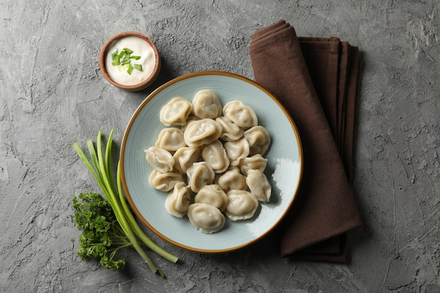 Assiette avec boulettes, serviette et épices sur fond gris, vue du dessus