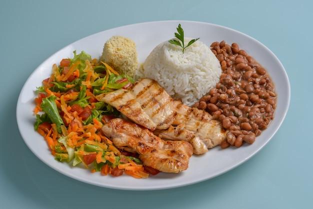 Assiette brésilienne d'aliments sains avec poitrine de poulet grillée haricots riz farine et salade de légumes