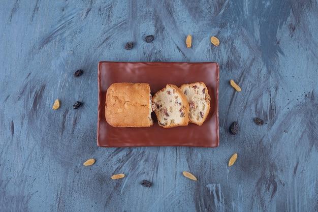 Assiette brune de gâteau aux raisins en tranches sur une surface en marbre.