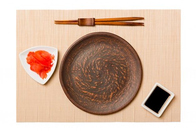 Assiette brune ronde vide avec des baguettes pour sushi et sauce soja, gingembre sur tapis de sushi brun. vue de dessus avec espace de copie pour votre conception