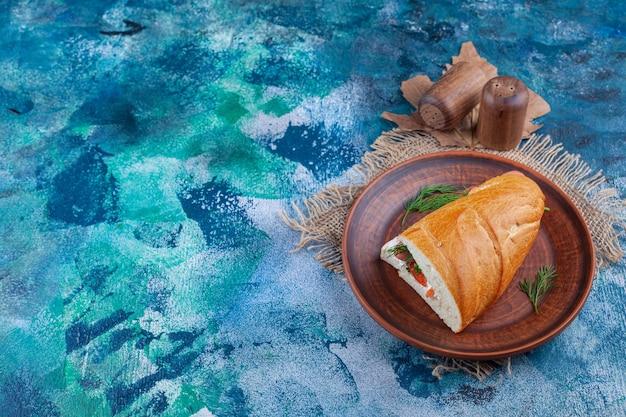 Une assiette brune de sandwich frais avec des épices sur un sac.