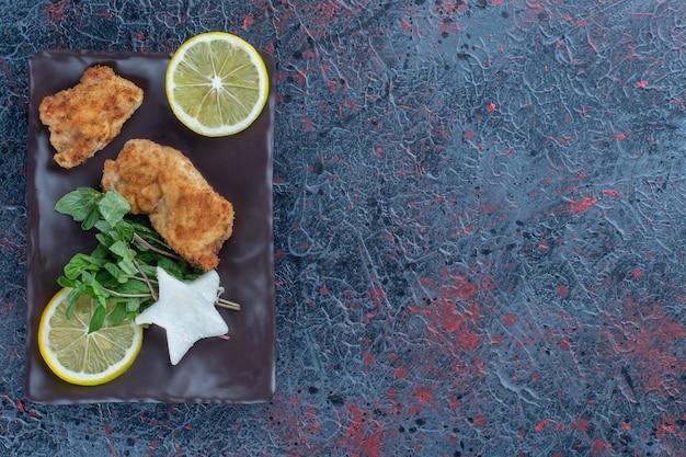Une assiette brune de viande de poulet à la menthe et des tranches de citron.