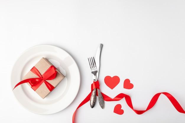 Assiette avec cadeau et couverts attachés avec un ruban rouge