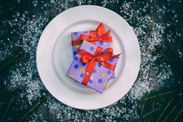 Assiette avec un cadeau sur une surface en bois grise