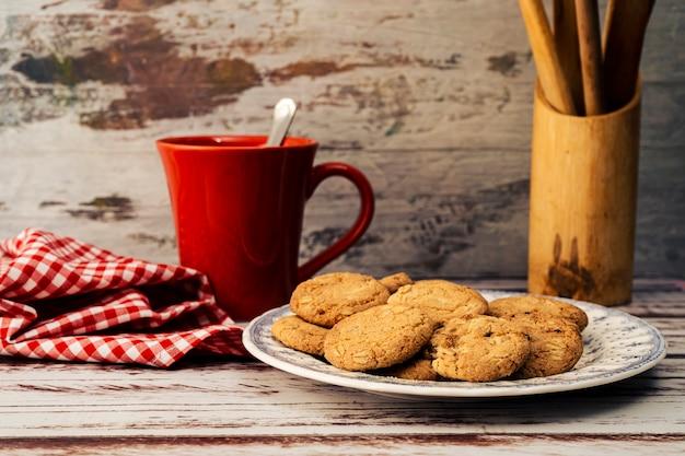 Assiette de campagne classique avec biscuits à l'avoine, une tasse rouge et une serviette