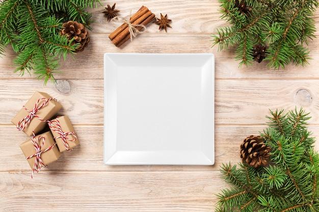 Assiette carrée blanche sur une table avec décoration de noël