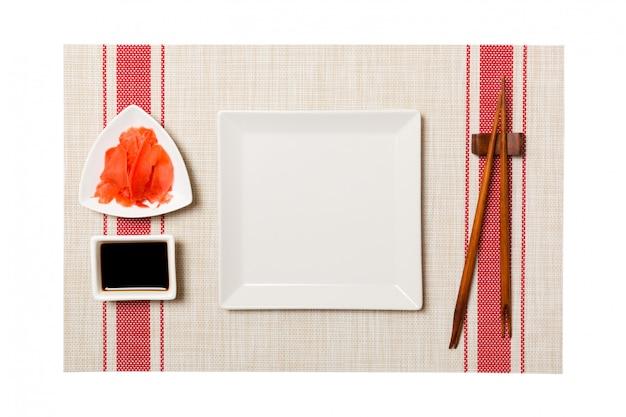 Assiette carrée blanche vide avec des baguettes pour sushi et sauce soja, gingembre sur fond de tapis de sushi.