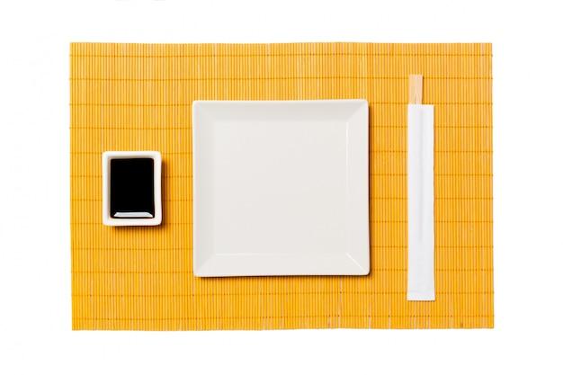 Assiette carrée blanche vide avec des baguettes pour sushi et sauce soja sur un tapis de bambou jaune. vue de dessus avec espace de copie pour votre conception