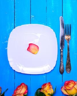 Assiette carrée blanche vide et couteau et fourchette en métal