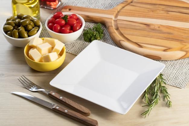 Assiette carrée blanche vide sur la table avec du fromage, des olives et des tomates cerises.