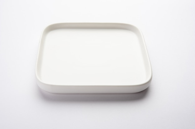 Assiette carrée en céramique blanche vide isolé sur fond blanc