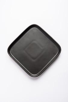 Assiette carrée en céramique noire vide isolé sur fond blanc
