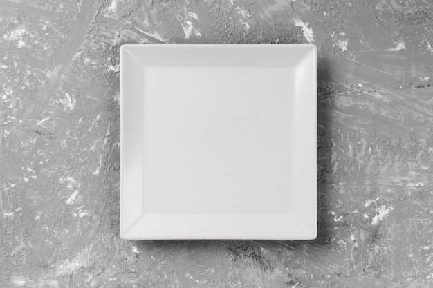 Assiette carrée sur le fond d'une table grise