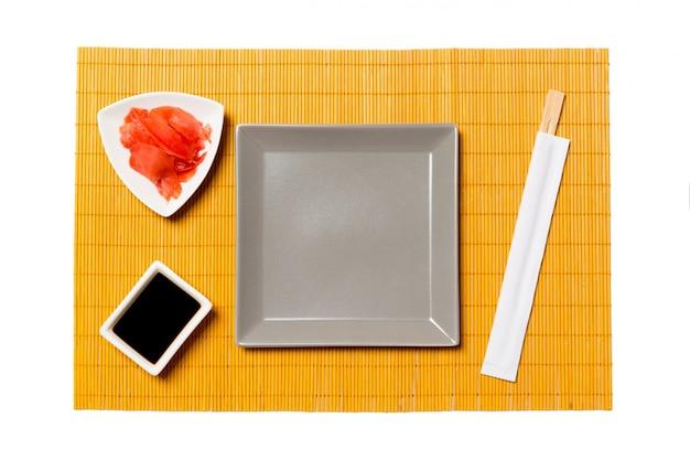 Assiette carrée grise vide avec des baguettes, du gingembre et de la sauce de soja sur un tapis de bambou jaune