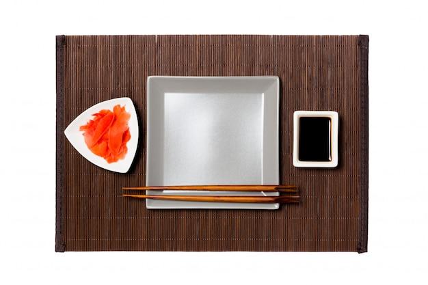 Assiette carrée grise vide avec des baguettes pour sushi sur tapis de bambou foncé