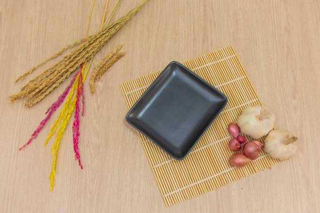 Une assiette carrée noire a été placée sur la table et du riz à l'ail, des oignons ont été placés autour.