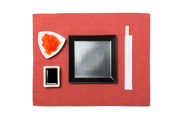 Assiette carrée noire vide avec des baguettes pour sushi, gingembre et sauce soja sur serviette rouge