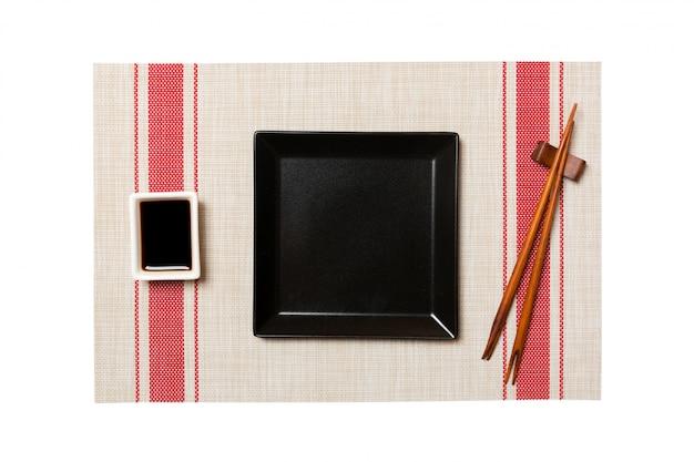Assiette carrée noire vide avec des baguettes pour sushi et sauce soja sur tapis de sushi