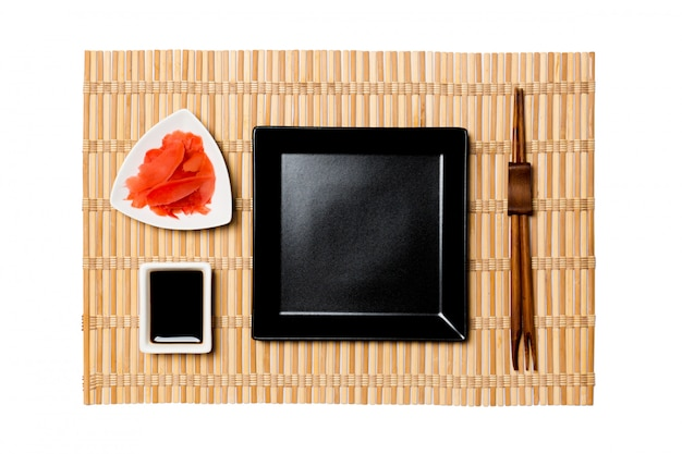 Assiette carrée noire vide avec des baguettes pour sushi sur tapis en bambou jaune