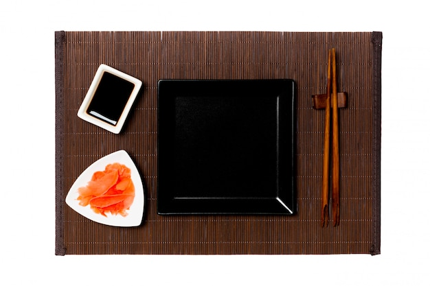 Assiette carrée noire vide avec des baguettes pour sushi