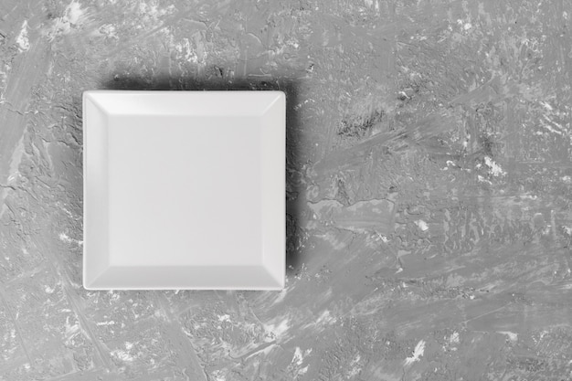 Assiette carrée vide sur sombre texturé
