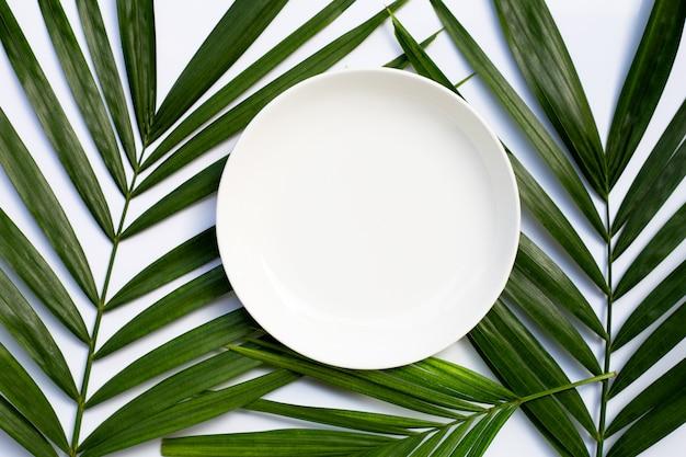 Assiette en céramique blanche vide sur les feuilles de palmier tropical sur fond blanc.