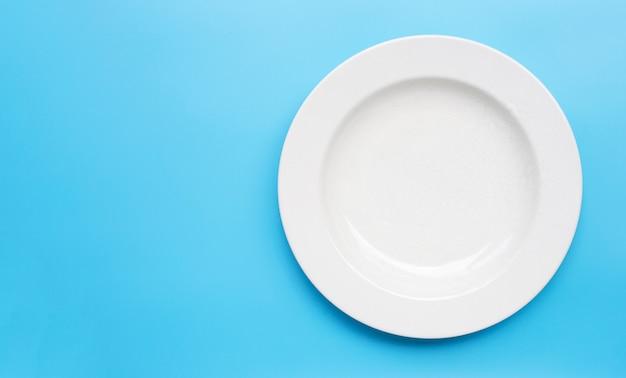Assiette en céramique blanche vide sur fond bleu.